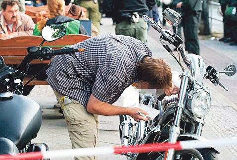 Ein Ermittler untersucht eines der bei der Razzia beschlagnahmten Motorräder. Foto: Theo Schneider