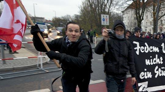 Rechte Gewalt in Berlin: Ein Neonazi stürm auf einen Fotografen zu und attackiert ihn mit einem Fahnenstock © A. Reiter