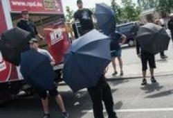 Rechtsextreme Hetzer verschanzen sich bei Sonnenschein hinter Regenschirmen; Photo: Theo Schneider