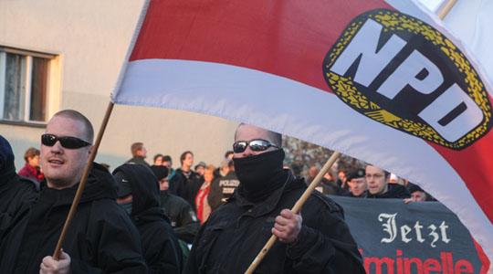 Ein NPD-Aktivist mit Fahne auf einem Aufmarsch in Berlin © Theo Schneider<br />